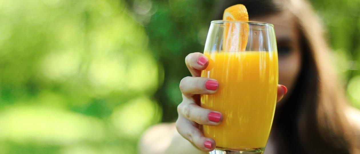 Žena drži čašu soka od naranče
